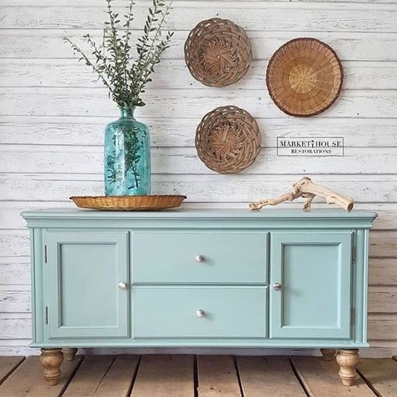 Robin egg blue dresser and vase against a white shiplap wall