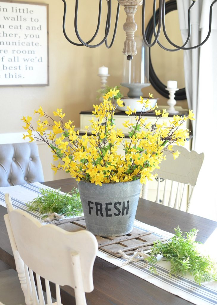 Bright yellow forsythia in a galvanized bucket on a dining room table