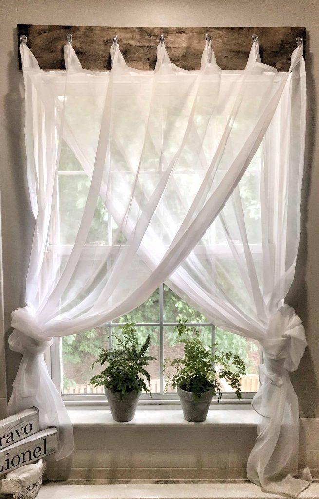 Sheer white curtain panels on a farmhouse window