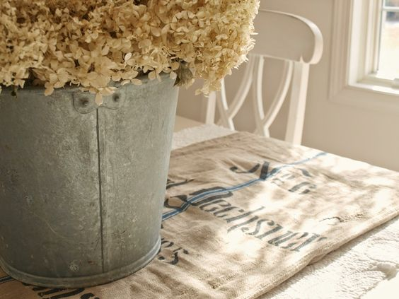 Cream colored dried flowers in a galvanized bucket on a white farm table