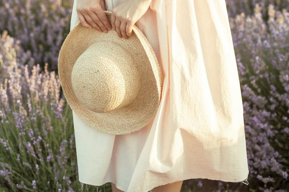 Woman holding a straw hat in a white cotton dress