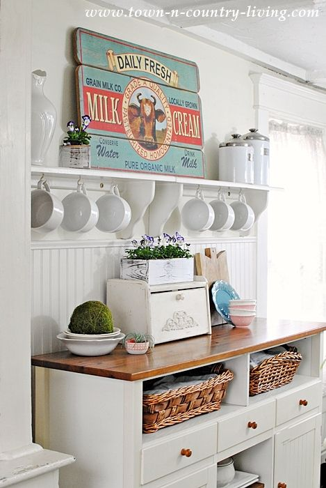 Aqua and coral metal sign on a white shelf with mugs and kitchen countertop