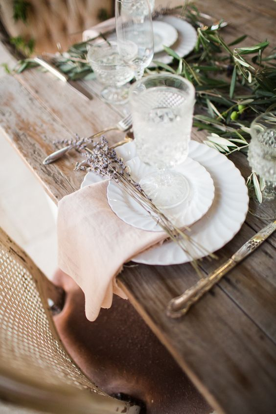 Vintage white dishes with pale rose napkin on a wood table with silver accents