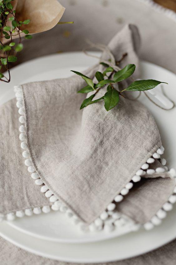 Oatmeal linen napkins with white pom pom trim on a white plate