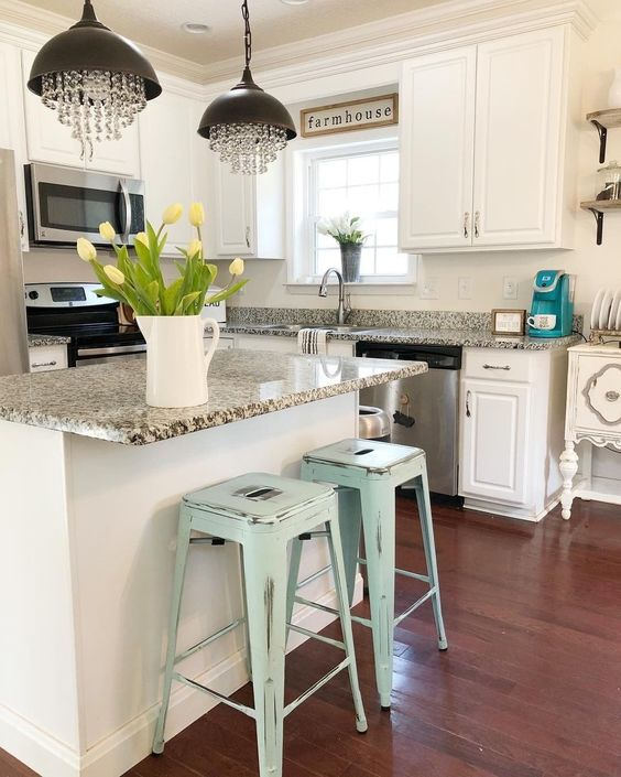White farmhouse kitchen accented with light blue metal stools and crystal chandelier