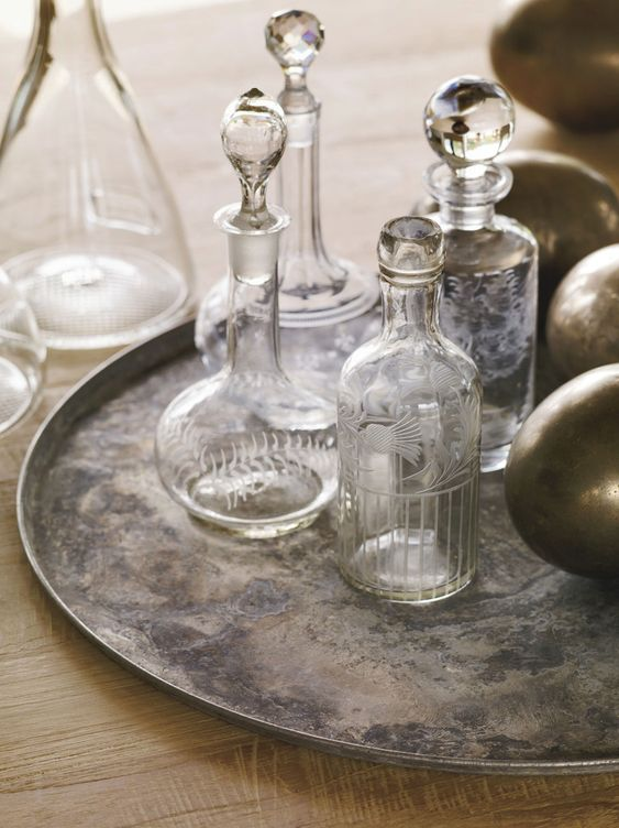 Vintage glassware and wine decanters on a distressed engraved tray