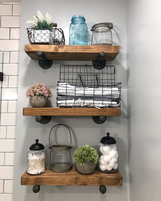 Thick wooden shelves with iron supports mixed with glass apothecary jars and wire storage