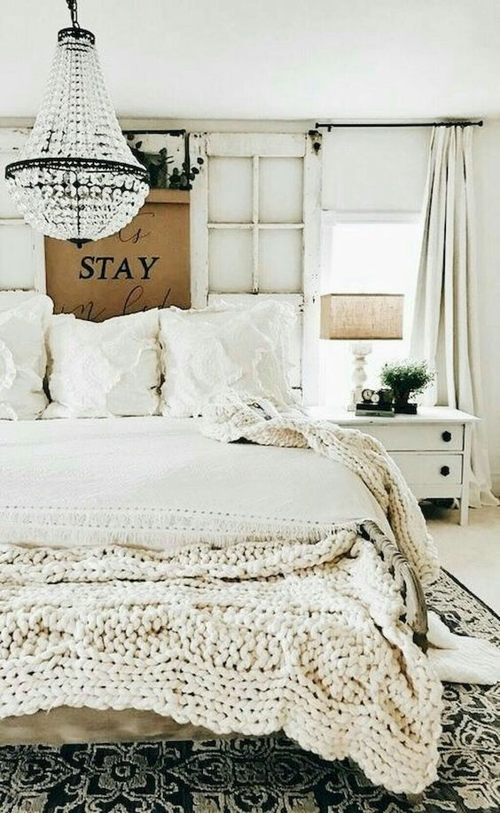 Chunky textured bedspread in a white country bedroom with crystal chandelier