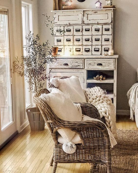 Farmhouse style room with distressed paint finishes and a wicker chair