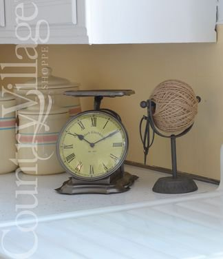 Vintage style scale clock and iron twine holder with scissors on a kitchen counter