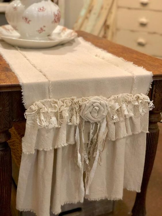 Oatmeal colored linen table runner with fabric roses and ruffles