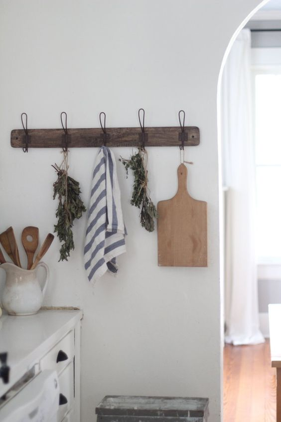Wall hooks with wooden cutting boards, dishtowels, and dried lavender in a kitchen