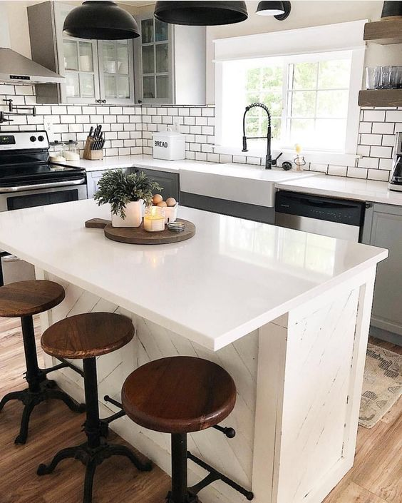 Clean white modern kitchen with vintage wooden stools and farmhouse faucet