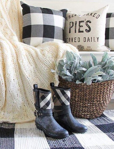 Black rain boots with black and white buffalo check accents in front of a knitted throw blanket and buffalo check pillow