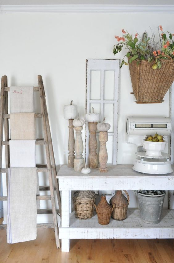 Room setting including ladder display, wood candlesticks, white farm table, and vintage pots
