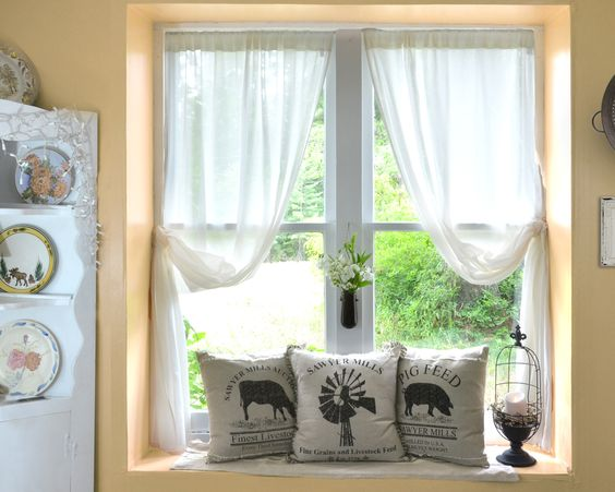 Three pillows with farm animal motif, with white sheer curtains in summer