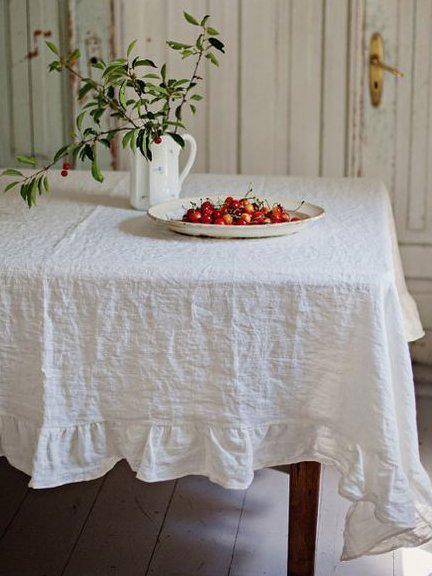 Farm table with white muslin tablecloth and table decorations