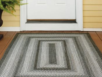 Rectangular braided rug in gray and black in front of an entry door