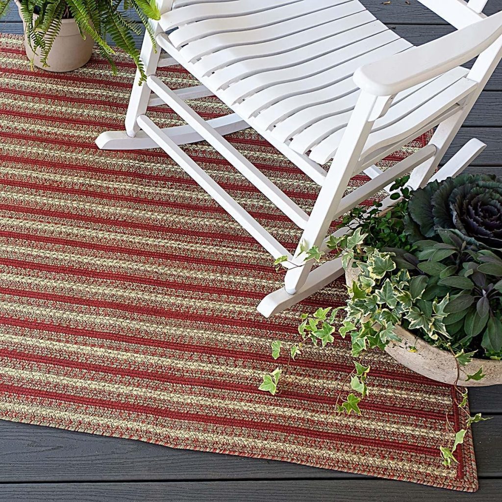 Striped red and tan rug under a white wooden porch rocker