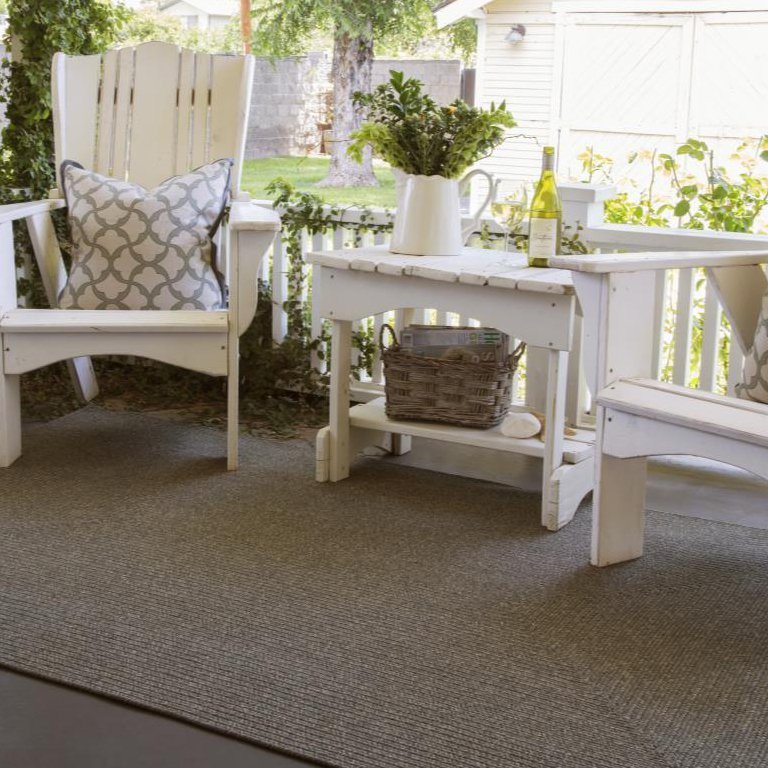 Slate gray solid braided rug on porch with white wooden country porch furniture