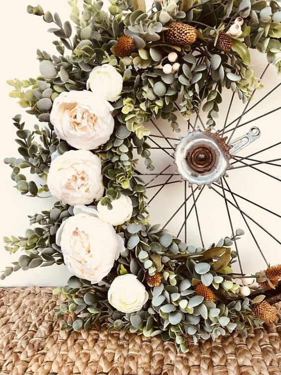 Wreath with eucalyptus and garden roses around a bicycle rim