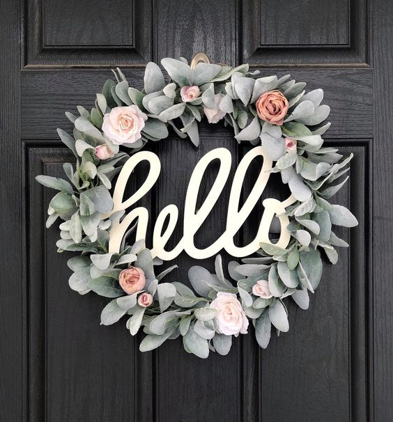 Eucalyptus wreath with pale pink garden roses and the word hello in the center