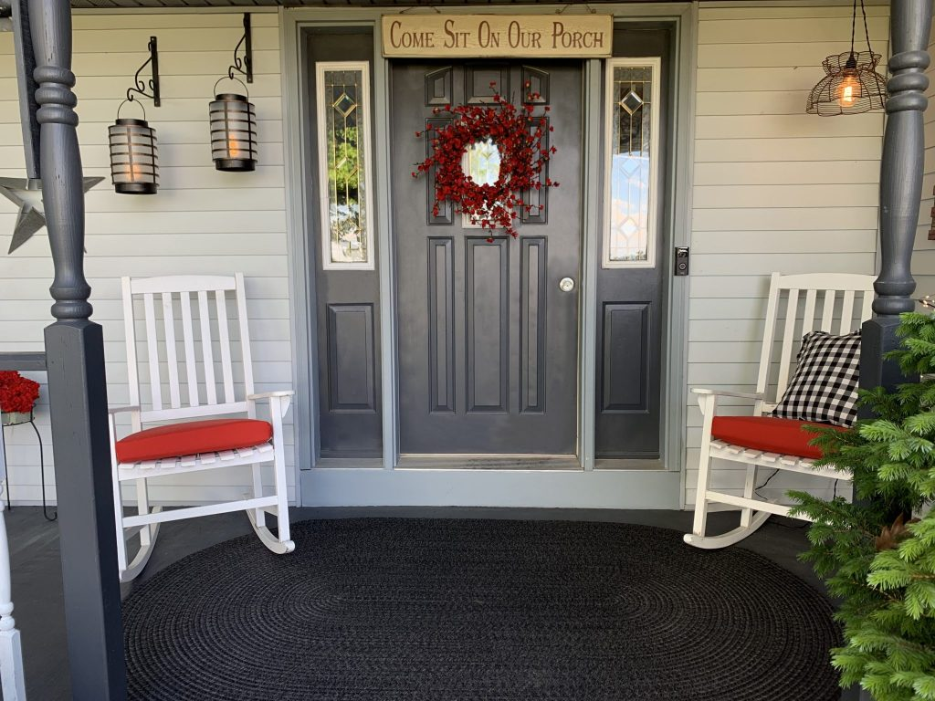 Front porch in gray with white chairs, porch lanterns, red wreath and wall decor