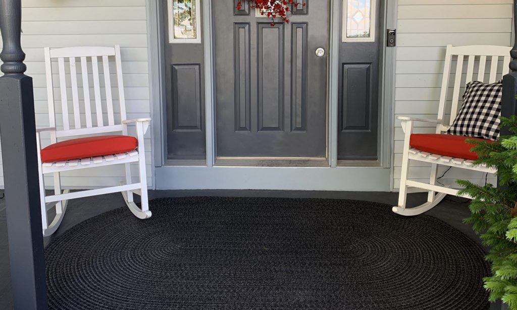 Black oval braided rug in front of entry door on front porch