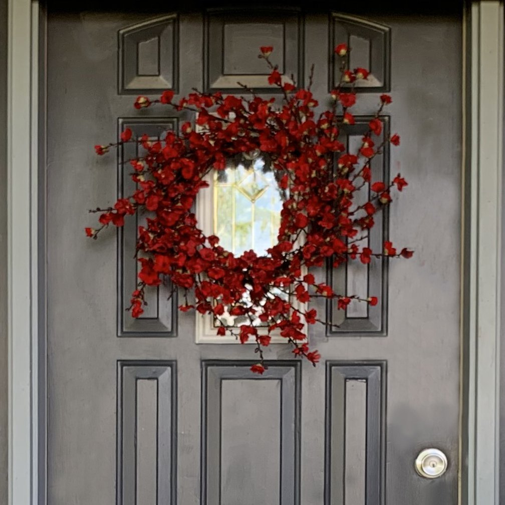 Red floral wreath on a black traditional door
