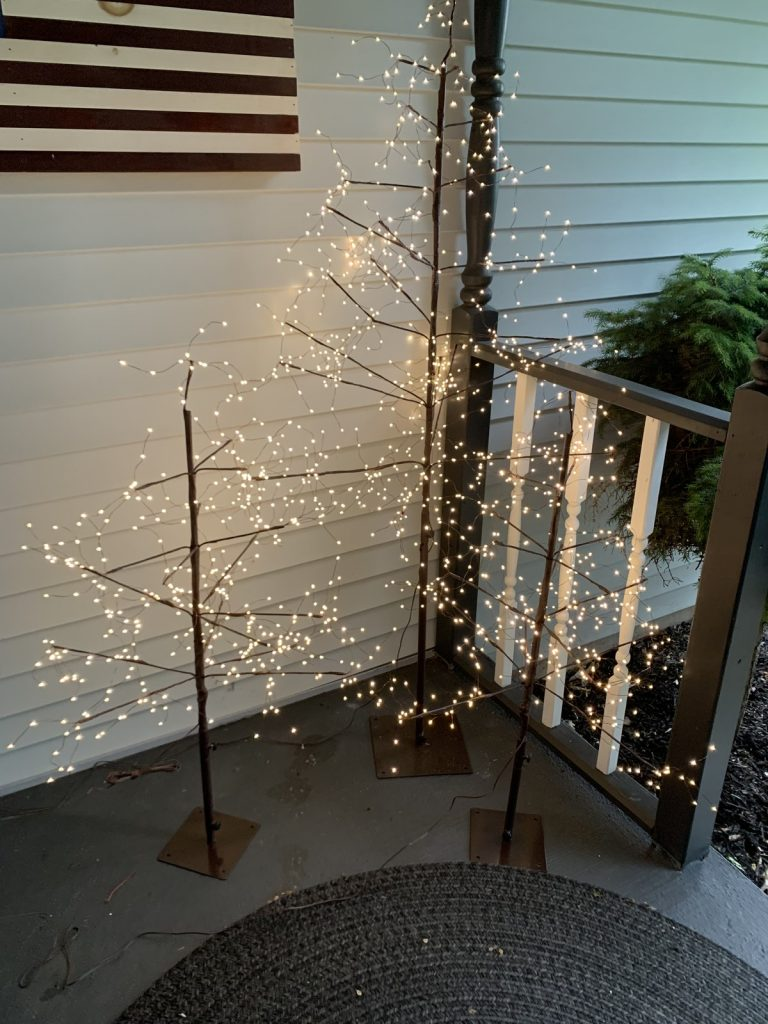 Three lighted trees on country porch