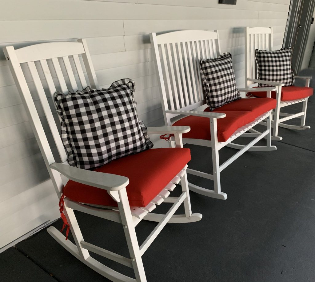 White wooden country porch rockers with red cushions and black and white buffalo check pillows