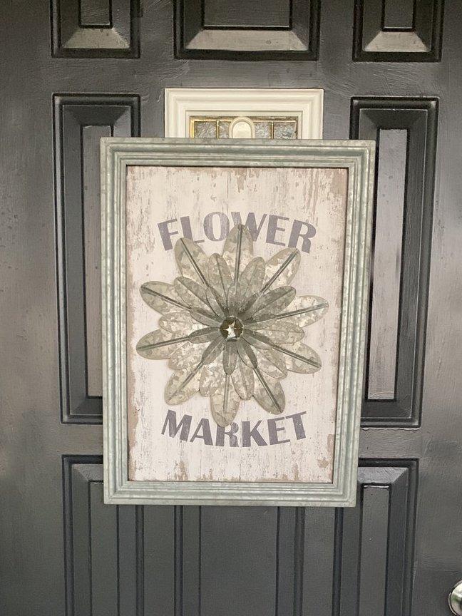 """Framed """"flower market"""" decoration on a black panel front door"""