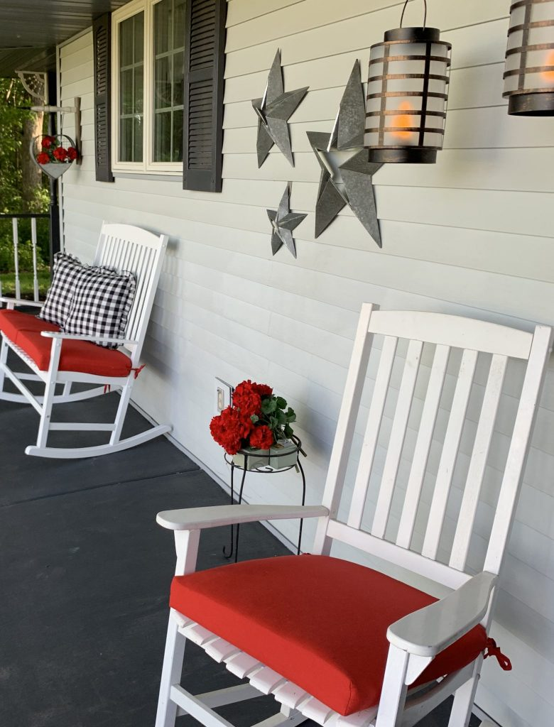 Gray front porch with white country rockers with red cushions