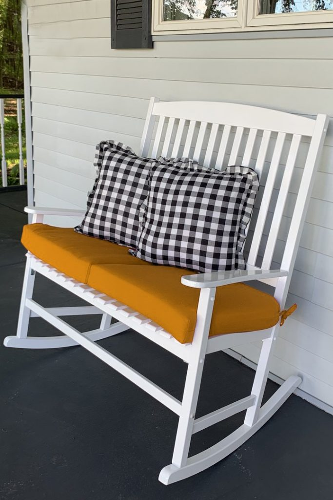 Gold cushions and buffalo check pillows on a country style white porch rocker