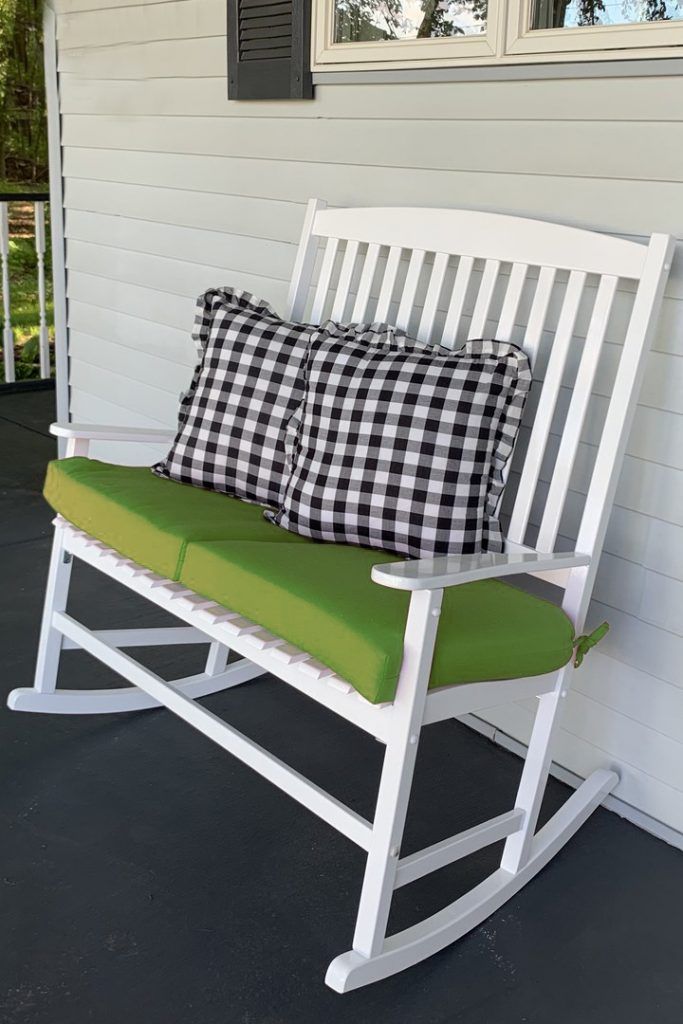 Double wooden porch rocker with green cushions and buffalo check pillows