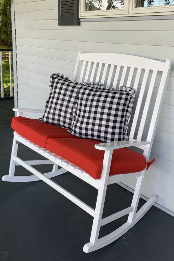 White wooden double rocker with red cushion and buffalo check pillows