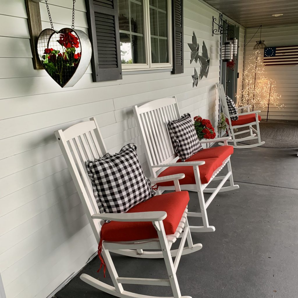 Side view of porch with white rocking chairs, red cushions, country decor